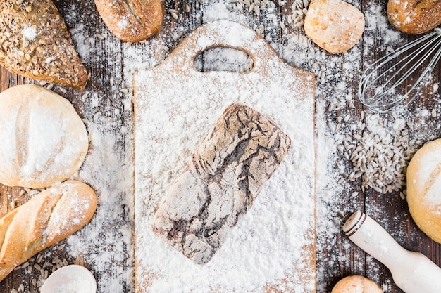 Vue aérienne de la farine répartie sur le pain cuit au-dessus de la table en bois