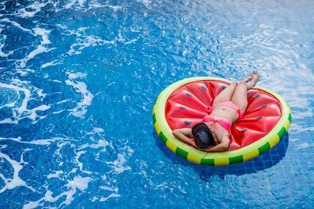 Vue aérienne de la femme en bikini se trouvant sur un matelas flottant dans la piscine.