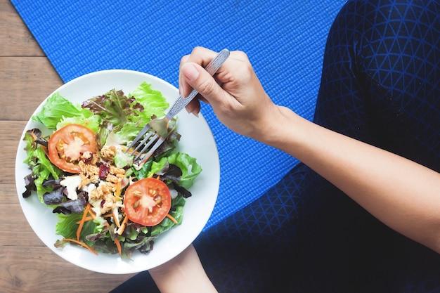Vue aérienne de la femme du yoga qui mange de la salade fraîche, une alimentation saine et un concept de travail