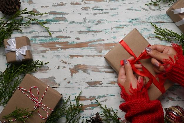 Vue aérienne femme en pull rouge enveloppant des cadeaux de noël sur un fond en bois.