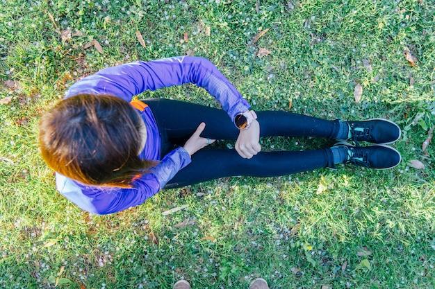 Vue aérienne d'une femme regardant une montre intelligente au sol dans un parc avec de l'herbe regardant le concept de pente d'entraînement sport et technologie à l'extérieur