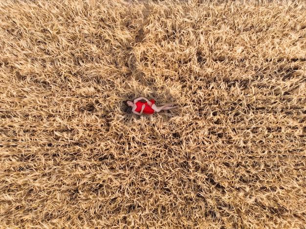 Vue aérienne de la femme en robe rouge allongée dans le champ de blé jaune
