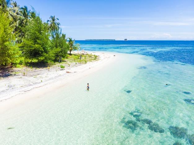 Vue aérienne: femme sortant de la mer des caraïbes, eaux turquoise d'une île tropicale