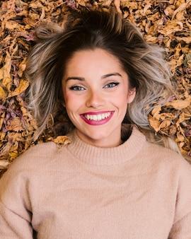 Vue aérienne de femme souriante allongée sur des feuilles sèches, regardant la caméra