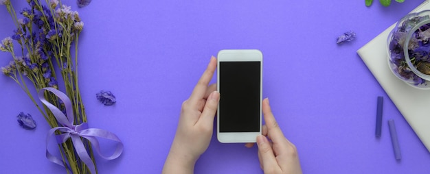 Vue aérienne d'une femme tenant un smartphone sur une table violette