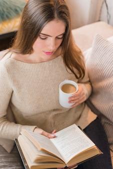 Vue aérienne, de, femme, tenue, tasse café, livre lecture