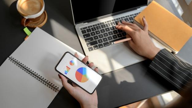 Vue aérienne d'une femme travaillant sur un ordinateur portable tout en regardant le tableau des affaires sur smartphone
