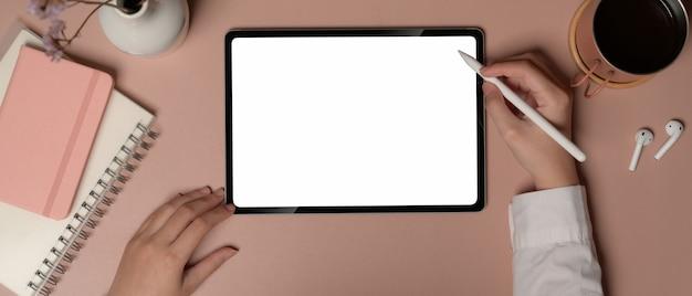 Vue aérienne d'une femme travaillant avec une tablette numérique sur un bureau rose avec des cahiers et des accessoires, un tracé de détourage.