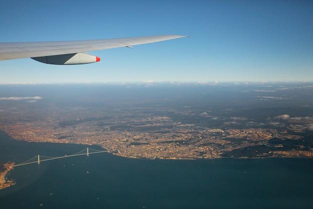 Vue aérienne de la fenêtre de l'avion sur le pont akashi-kaikyo traversant la baie d'osaka au japon