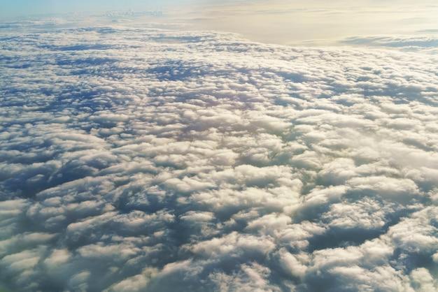 Vue aérienne de la fenêtre de l'avion regardant la lumière du matin au-dessus des nuages et du ciel