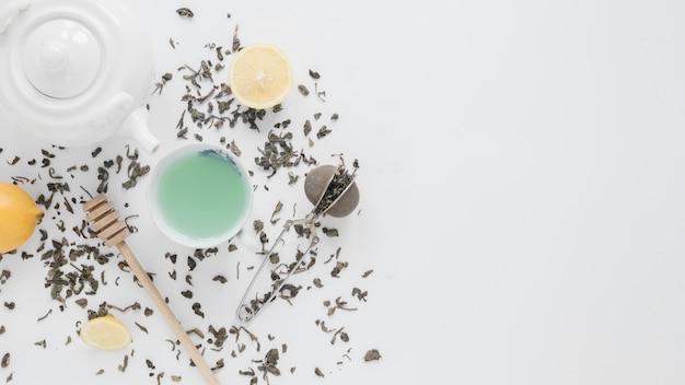 Une vue aérienne de feuilles de thé sèches; passoire à thé; citron; thé vert; louche de miel et théière sur fond blanc