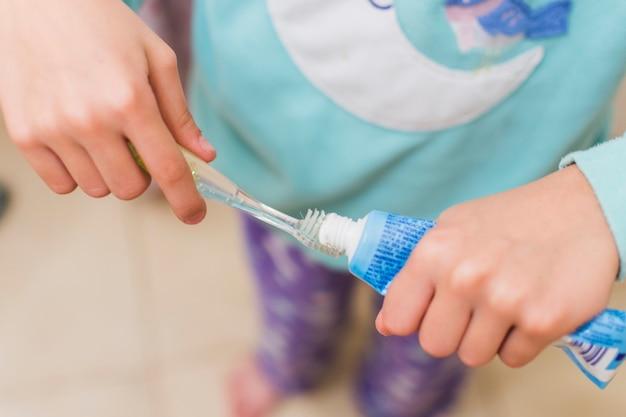 Vue aérienne de la fille en plaçant le dentifrice sur la brosse à dents