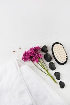Une vue aérienne de fleurs d'aster; serviette; pierre spa et brosse de massage sur sel sur fond blanc