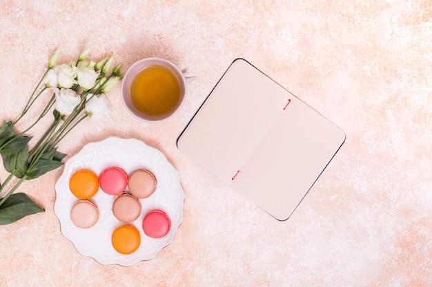 Une vue aérienne de fleurs d'eustoma; tasse de thé vert; macarons sur une plaque blanche et bloc-notes vide sur fond rustique