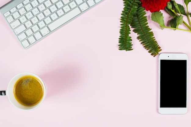 Une vue aérienne de fougère; fleur rouge; clavier; smartphone et tasse de thé sur fond rose