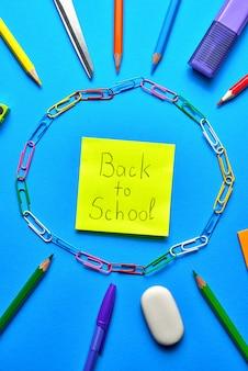 Vue aérienne de fournitures scolaires sur un bleu vibrant
