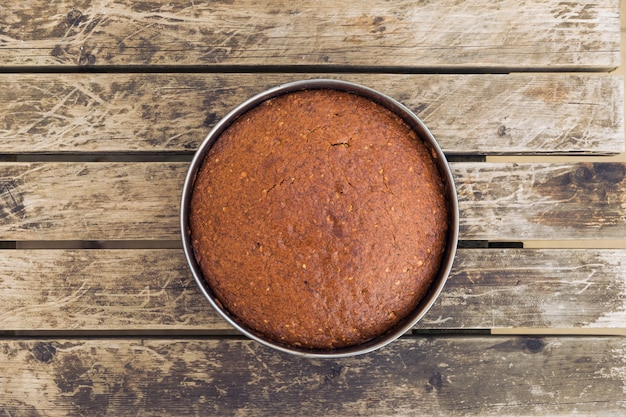 Vue aérienne d'un gâteau délicieusement cuit au four dans un moule rond sur une surface en bois