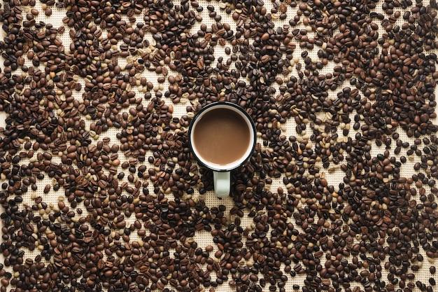 Vue aérienne de grains de café torréfiés et d'une tasse à café