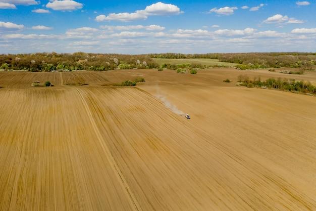 Vue aérienne grand tracteur cultivant un champ sec