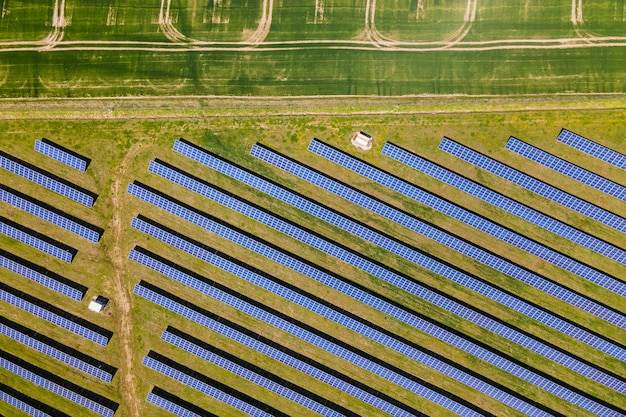 Vue aérienne d'une grande centrale électrique durable avec de nombreuses rangées de panneaux solaires photovoltaïques pour la production d'énergie électrique écologique propre. électricité renouvelable avec concept zéro émission.