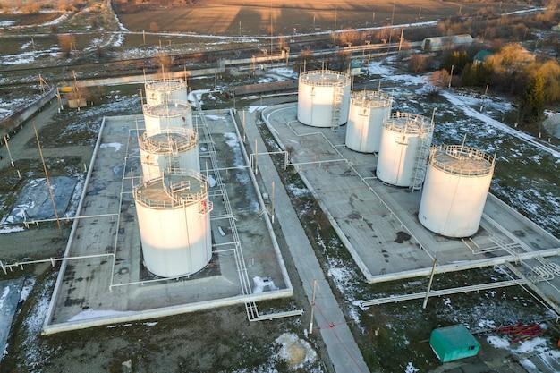 Vue aérienne de grands réservoirs de carburant en zone industrielle pétrolière en hiver.