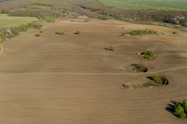 Vue aérienne gros tracteur cultivant un champ sec. vue aérienne de haut en bas du tracteur cultivant le sol et ensemencant un champ sec. tracteur aérien coupe des sillons dans le champ de la ferme pour le semis.