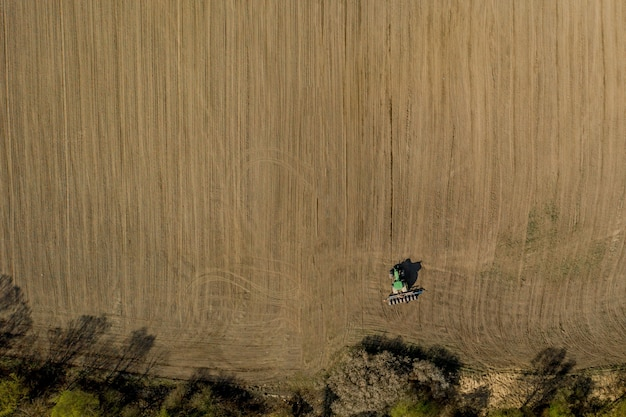 Vue aérienne gros tracteur cultivant un champ sec. vue aérienne de haut en bas du tracteur cultivant le sol et ensemencant un champ sec