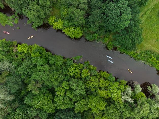 Vue aérienne d'un groupe de kayaks voyageant sur une rivière forestière un jour d'été