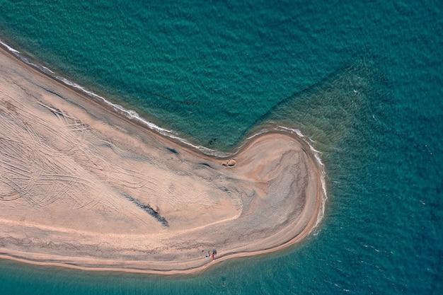 Vue aérienne de haut en bas d'une longue plage de sable étroite s'étendant dans la mer turquoise