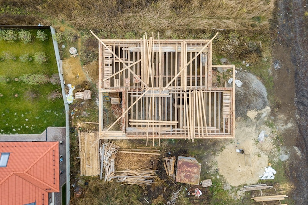 Vue aérienne de haut en bas d'une maison en construction avec charpente en bois.