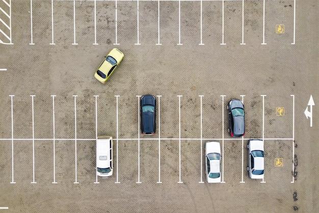 Vue aérienne de haut en bas de nombreuses voitures sur un parking de supermarché ou sur le marché des concessionnaires automobiles en vente.