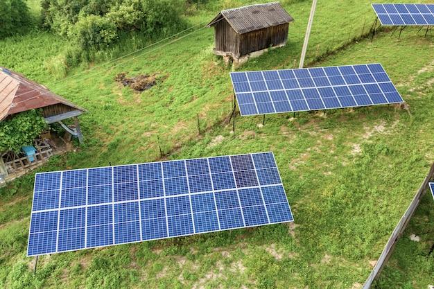 Vue aérienne de haut en bas des panneaux solaires dans une zone rurale verte.