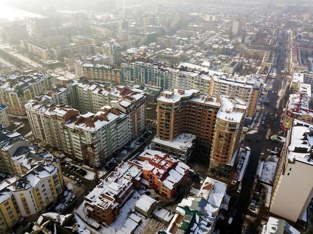 Vue aérienne d'hiver noir et blanc du centre de la ville moderne avec de grands bâtiments et voitures en stationnement dans les rues enneigées.