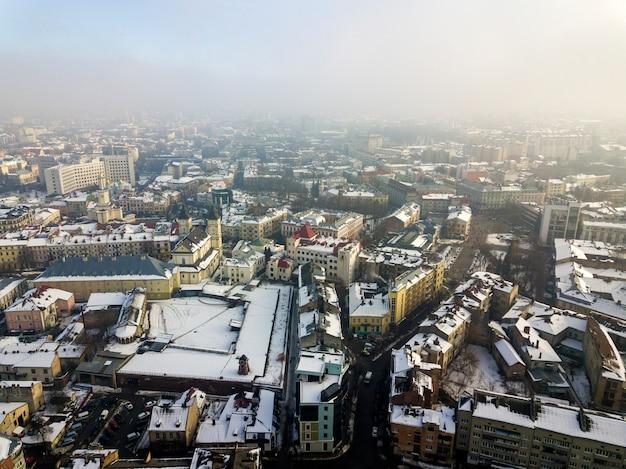 Vue aérienne d'hiver noir et blanc du centre-ville moderne avec de grands immeubles et des voitures garées dans les rues enneigées.
