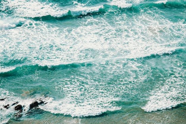 Vue aérienne horizontale des vagues sur une plage d'eau cristalline