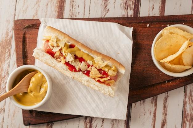 Vue aérienne d'un hot-dog avec de la moutarde, du ketchup et garni de morceaux de croustilles. vue horizontale. concept de restauration rapide et de malbouffe.
