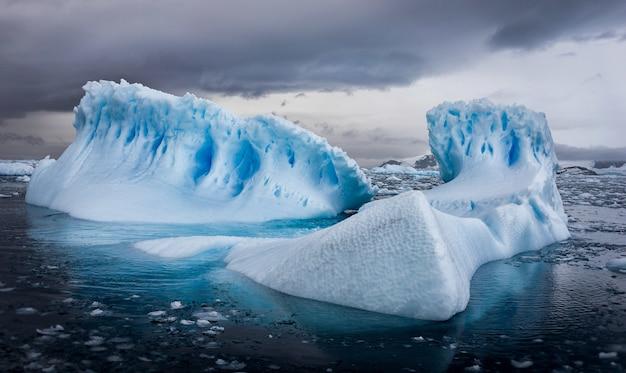 Vue aérienne d'icebergs en antarctique sous un ciel nuageux