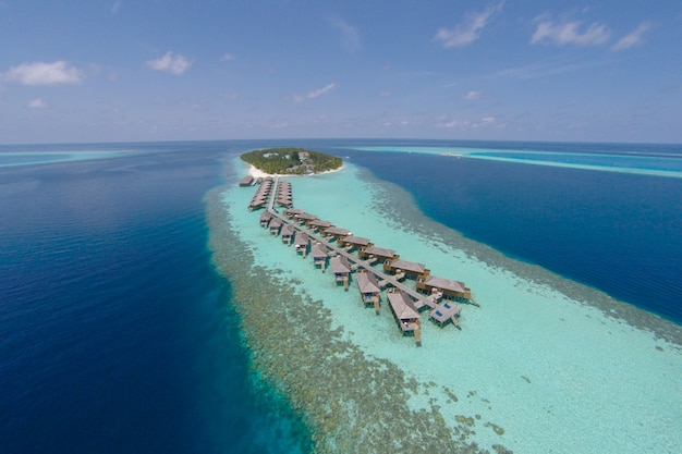 Vue aérienne d'une île tropicale en eau turquoise. villas luxueuses sur l'eau sur les îles tropicales de maldives pour les vacances, concept de fond de vacances - traitement des couleurs haut de gamme.