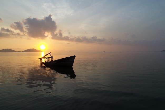 Vue aérienne d'une île tropicale et d'un vieux bateau au coucher du soleil à phuket en thaïlande