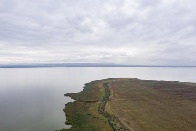 Vue aérienne à l'immense lac avec un sre vert et ciel en début de soirée
