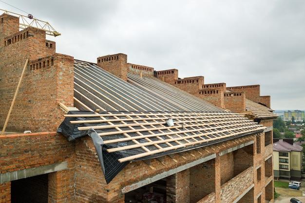 Vue aérienne d'un immeuble en briques inachevé avec une structure de toit en bois en construction.