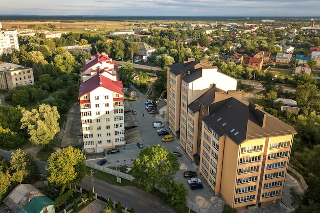 Vue aérienne d'immeubles d'habitation de plusieurs étages dans un quartier résidentiel verdoyant.
