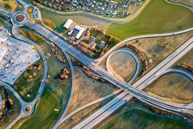 Vue aérienne de l'intersection de la route moderne, les toits des maisons sur fond de champ vert de printemps. photographie de drone.