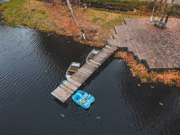 Vue aérienne de la jetée avec des bateaux en bois au bord d'un lac pittoresque, forêt d'automne. saint-pétersbourg, russie.