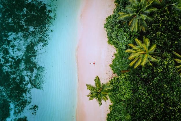 Vue aérienne d'une jeune femme se détendre sur la plage de sable du paradis tropical entouré de palmiers et d'eau peu profonde de l'océan azur cristallin.