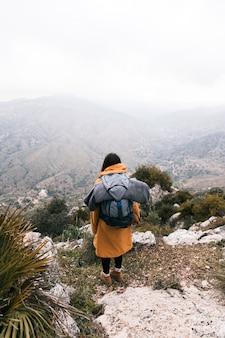 Une vue aérienne d'une jeune femme avec son sac à dos surplombant la montagne