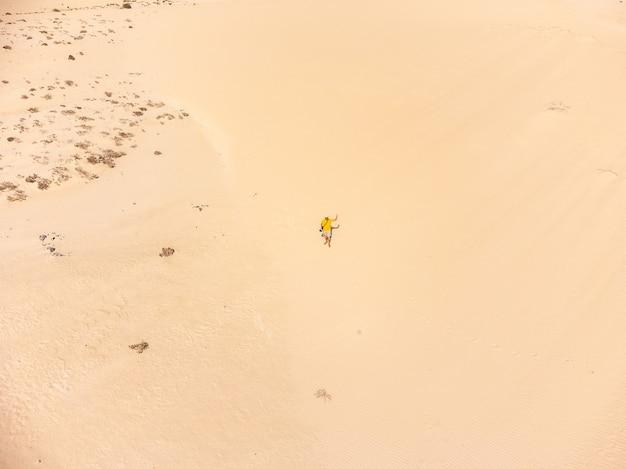 Vue aérienne d'un jeune homme pilotant le drone dans les dunes du parc de corralejo, fuerteventura, îles canaries. espagne