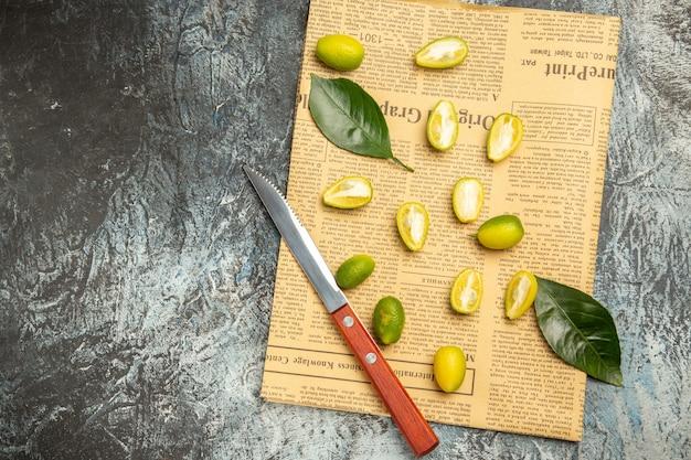 Vue aérienne des kumquats frais coupés en deux sur des journaux sur fond gris
