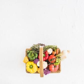 Une vue aérienne de légumes frais dans le panier sur le fond texturé