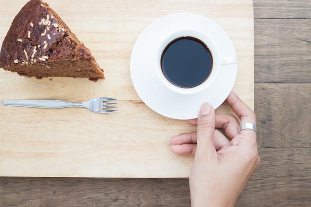 Vue aérienne de la main de femme tenant une tasse de café et un morceau de gâteau